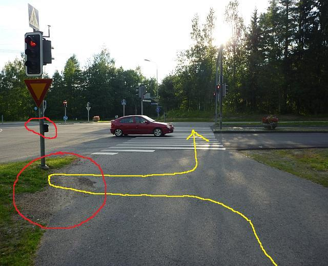 Liikennevalot Keskussairaalantien ja Savelankadun risteyksessä. Liikennesääntöjen mukainen ajoreitti on merkitty keltaisella, risteyksen ongelmat punaisella.
