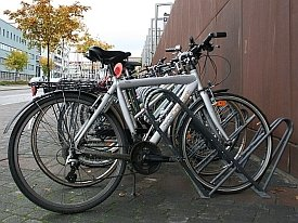 Esimerkiksi tällainen telinemalli on huomattavasti parempi. Teline tukee pyörää ja pyörän voi runkolukita aisaan. JYPS on ollut mukana telineen suunnittelussa. Tuotantomallissa pyöräpaikat on valitettavasti sijoitettu liian lähekkäin.