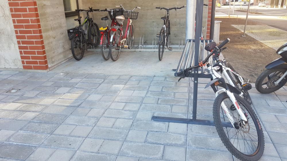 Kun pyörätelineessa ei ole runkolukitusmahdollisuutta, niin pyöriä kiinnitetään lähiseudun tolppiin ja kaiteisiin, tässä mattotelineeseen. Kuva Jyväskylän Kankaan uudelta asuinalueelta, jolla pyöräpysäköintiin piti kiinnittää tavanomaista enemmän huomiota.