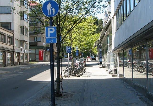 Tämä pyöräparkki sijaitsee jalkakäytävällä. Jalkakäytävillä pyörällä ajamista pyritään vähentämään, mutta samaan aikaan pyöräparkkeja sijoitetaan jalkakäytäville.