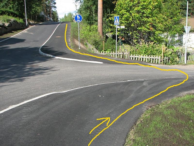 Mutkittelevaa kävely- ja pyöräilylinjaa risteyksessä. Kävelijät ja pyöräilijät ovat vielä risteyksen luona hetken matkaa selin viereiseen ajorataan nähden, joten muun liikenteen havainnointi on vaikeaa.