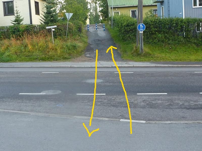 Yhdistetty jalkakäytävä ja pyörätie jatkuu ajoradan toisella puolella. Ongelmana on, ettei väylälle ole ajoreittiä. Ajorata pitäisi ylittää kohtisuoraan – matkalla on kaksi jyrkkää reunakiveystä ja poikittainen jalkakäytävä.