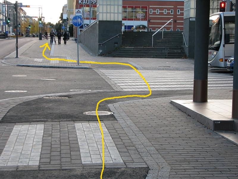 Pyörällä kulkemisen kannalta epäonnistunut risteys Jyväskylän Yliopistonkadulla. Kulkulinja on mutkitteleva. Jokaisessa ajoradan ja pyörätien yhtymäkohdassa on terävä reunakiveys.
